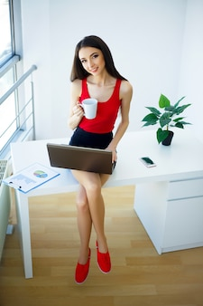 Die schöne junge frau, die im roten t-shirt und im schwarzen rock gekleidet wird, arbeitet an dem computer.
