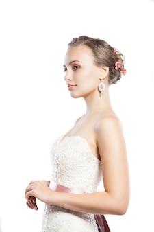 Die schöne junge frau, die in einem hochzeitskleid aufwirft. schönheits-make-up. schmuck