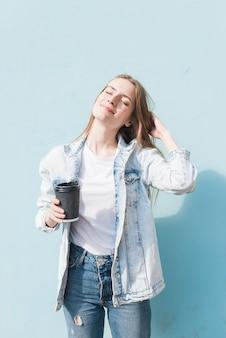 Die schöne junge frau, die wegwerfkaffeetasse mit augen hält, schloss stehende nahe wand