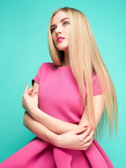 Die schöne junge frau im rosa minikleid posiert