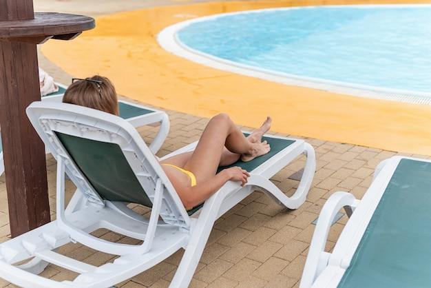Die schöne junge frau liegt auf der sonnenliege neben dem pool
