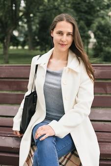 Die schöne junge frau sitzt lächelnd auf einer bank
