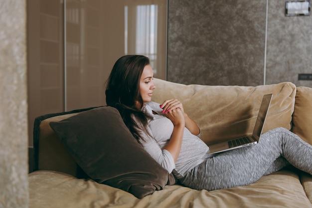 Die schöne junge frau zu hause liegt auf dem sofa, entspannt sich in ihrem wohnzimmer und arbeitet mit laptop