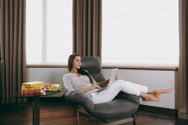 Die schöne junge frau zu hause sitzt auf einem modernen stuhl vor dem fenster, entspannt sich in ihrem wohnzimmer und arbeitet mit laptop
