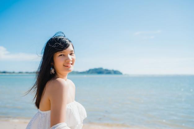Die schöne junge glückliche asiatin entspannen sich das gehen auf strand nahe meer.
