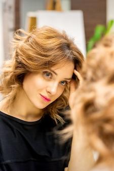 Die schöne junge kaukasische frau betrachtet ihr spiegelbild im spiegel und überprüft frisur und make-up in einem schönheitssalon.