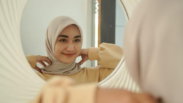 Die schöne junge muslimin lächelt süß im spiegel