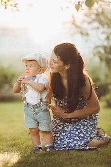 Die schöne junge mutter geht mit ihrem kleinen kaukasischen baby im park spazieren