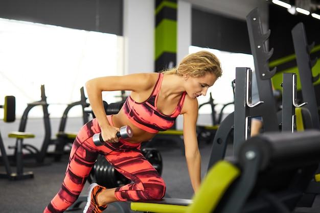 Die schöne junge sportliche frau, die sport tut, trainiert auf übungsmaschine in der turnhalle.