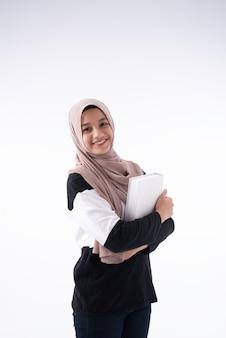 Die schöne moslemische frau, die buch in ihren armen umarmt
