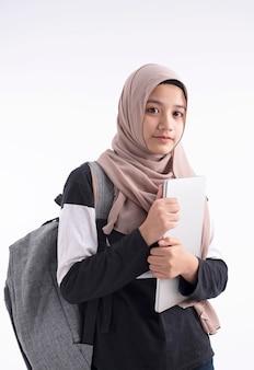Die schöne moslemische frau, die in der hand laptop hält