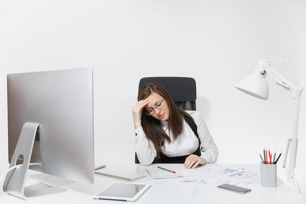 Die schöne müde, stressbraune geschäftsfrau mit kopfschmerzen, die am schreibtisch sitzt und an einem modernen computer mit modernem monitor mit dokumenten im hellen büro arbeitet,