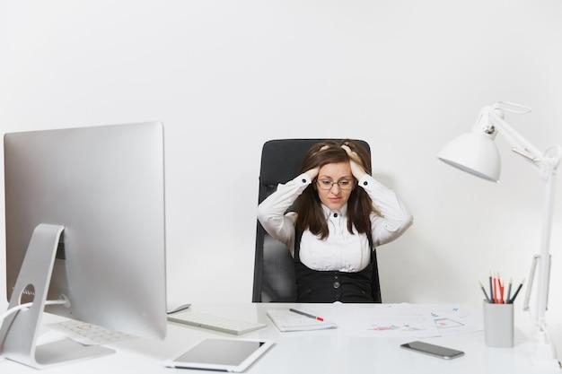 Die schöne müde verwirrte und gestresste braunhaarige geschäftsfrau in anzug und brille sitzt am schreibtisch und arbeitet an einem modernen computer mit dokumenten in einem hellen büro