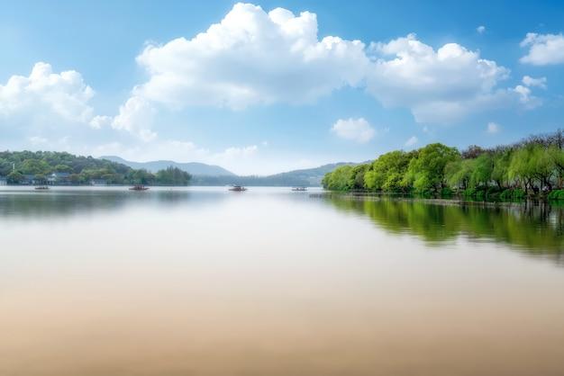 Die schöne naturlandschaft und holzboote des westsees in hangzhou