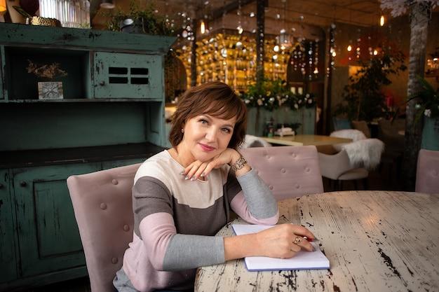 Die schöne, sachliche, erfolgreiche, erwachsene frau sitzt mit einem notizbuch und einem stift in einem café.