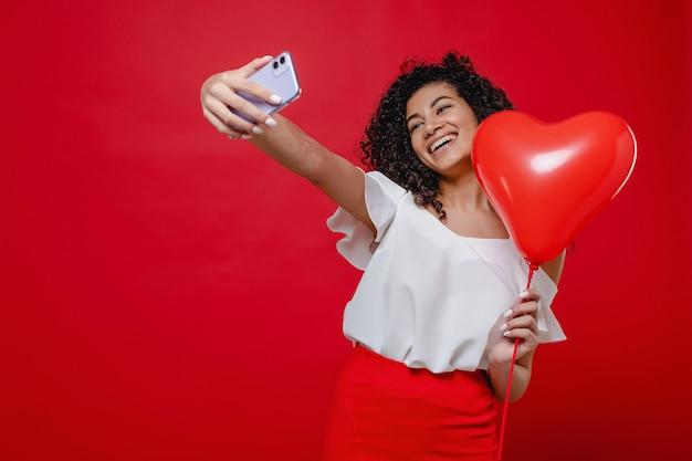 Die schöne schwarze frau, die selfie am telefon mit herzen macht, formte den ballon, der über rot lokalisiert wurde