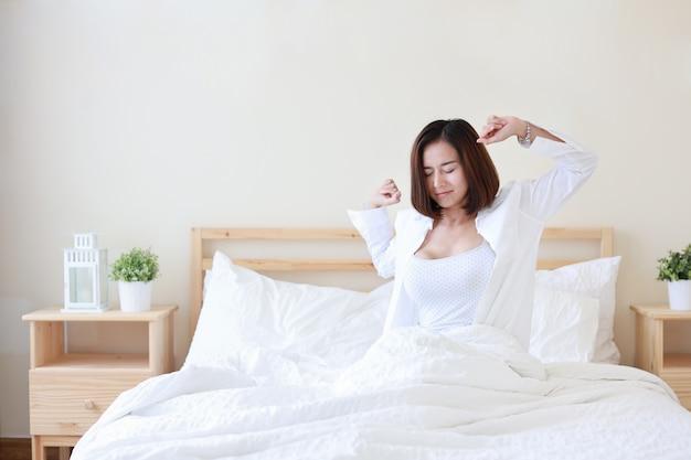 Die schöne und gesunde junge asiatische frau der vorderansicht wachen morgens auf