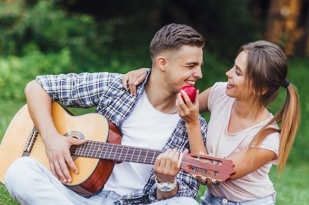 Die schönen brunettepaare, welche die picknickzeit im freien genießen, sind playinf an der gitarre