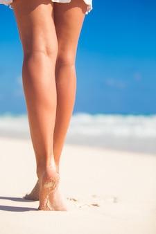 Die schönen glatten beine der frauen auf weißem sandstrand