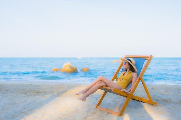 Die schönen jungen asiatischen frauen des porträts, die glücklich sind, entspannen sich lächeln um seestrandozean