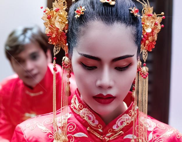 Die schönheit, die das rote kleid, stehend in der front trägt, verwischte gutaussehenden mann, porträt der vorbildlichen aufstellung, festival des chinesischen neujahrsfests, blendenfleckeffekt, undeutliches licht arund