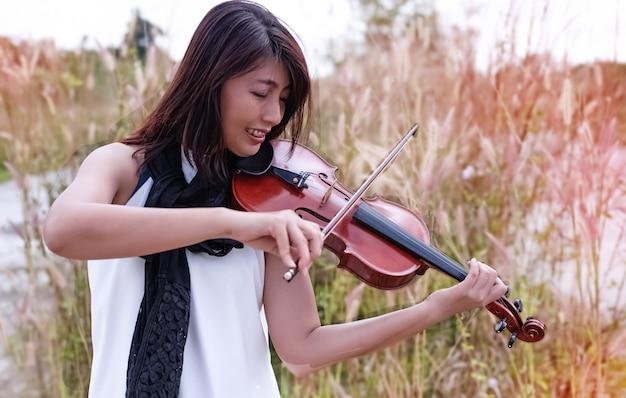 Die schönheit, die violine, mit glücklichem gefühl, vorbildliche aufstellung des porträts, seitenansicht des landes, undeutliches licht herum spielt