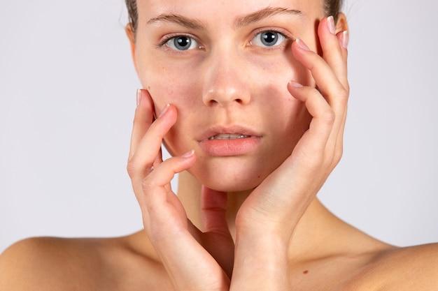 Die schönheit einer frau, gesunde haut und natürliches make-up. natürliche schönheit. spa-konzept, porträt auf weißer wand. hochwertiges foto