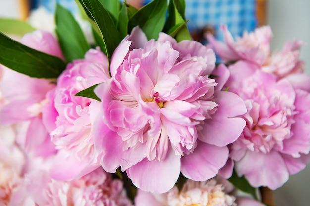 Die schönheit eines rosa pfingstrosenblumenstraußes in einem authentischen braunen koffer der weinlese.