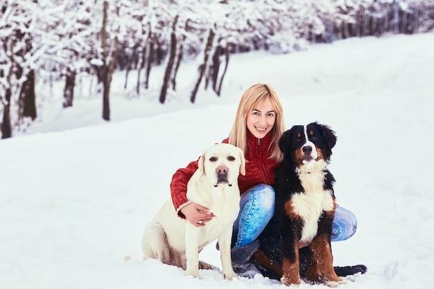 Die schönheit mit dem hund, der auf dem schnee sitzt