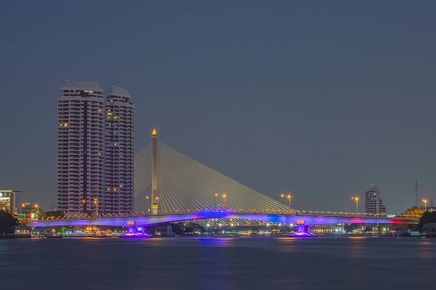Die schönheit von bunten lichtern auf pinklao-brücke und autos, die nachts auf chao phraya river fahren