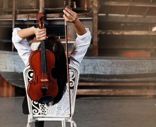 Die schönheitsdame, die mit dem hemd hält violine und bogen an der rückseite ihres kopfes trägt
