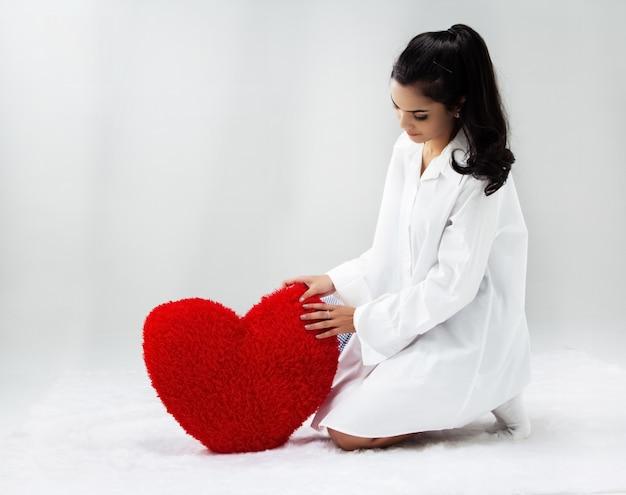 Die schönheitsdame trägt weißes hemd, legte rotes herzkissen in erdgeschoss