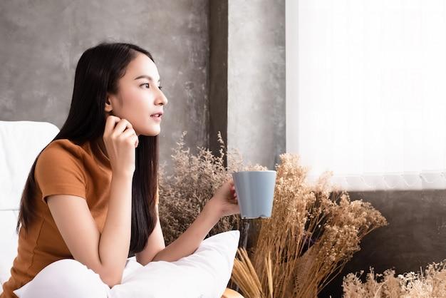 Die schönheitsfrau, die in der hand keramische kaffeetasse, äußeres fenster schauend hält