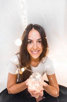 Die schöne junge Frau, die glühende Kugel mit Fähre hält, beleuchtet auf ihrem Kopf