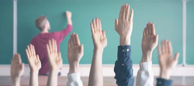 Die schüler in der schule mit erhobenen händen im klassenzimmer lernen zusammen