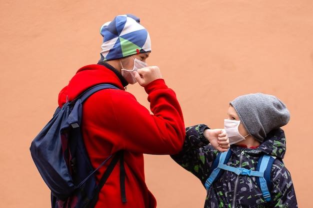 Die schüler in schutzmasken begrüßen sich mit den ellbogen