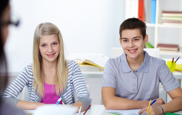 Die schüler sitzen und hören zu lehrer im klassenzimmer