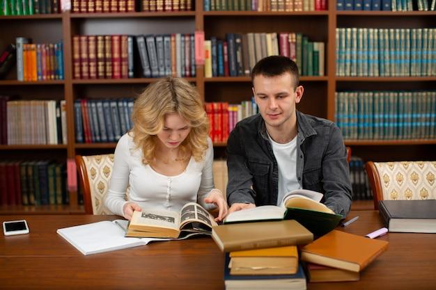 Die schüler sitzen zusammen in der bibliothek und lesen bücher