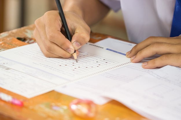 Die schülerhände, die prüfungen ablegen und prüfungsraum mit dem halten des bleistifts auf optischer form schreiben, beantwortet papierblatt auf dem schreibtisch, der abschlusstest im klassenzimmer durchführt. bildungsbewertungskonzept