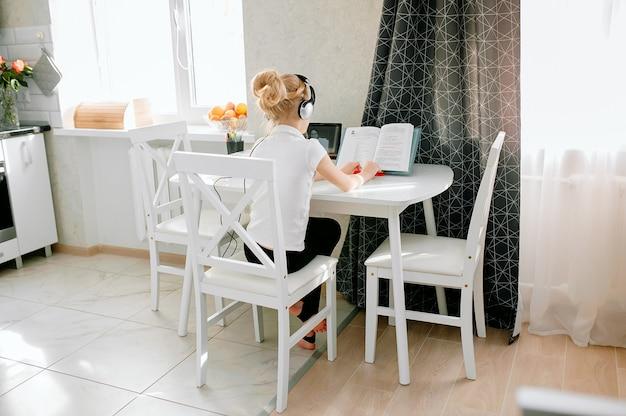 Die schülerin eines jugendlichen mädchens trägt eine telefonkonferenz, bei der sie online mit einem fernlehrer von zu hause aus lernt. teenager-student, der laptop verwendet, der in webcam-video-chat-lernstunde mit fernlehrer spricht.