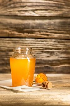 Die schüssel mit honig auf holztisch. die bank des honigs bleiben nahe hölzernem löffel
