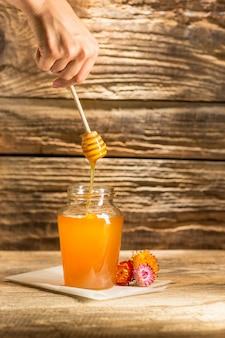 Die schüssel mit honig auf holztisch. die bank des honigs bleiben nahe hölzernem löffel Kostenlose Fotos