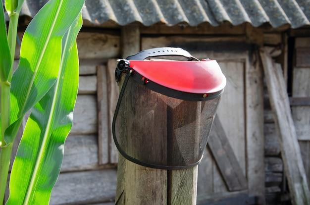 Die schutzmaske des gitters mit kopfhörern wiegt den benzinspießabzug aus der nähe