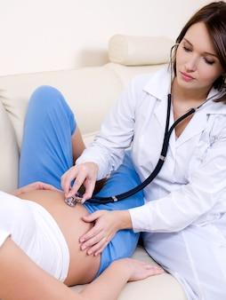 Die schwangere frau an der rezeption beim arzt