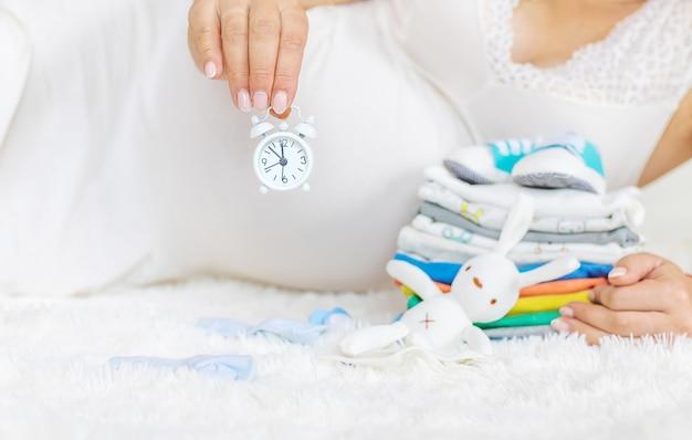 Die schwangere frau hält einen wecker in den händen.