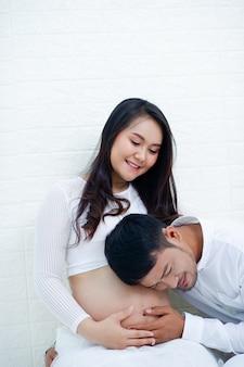 Die schwangere frau ist glücklich mit ihrem ehemann und bereitet sich darauf vor, das kind zu beobachten, das kurz vor der geburt steht.