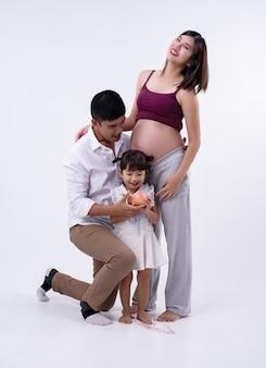 Die schwangere frau steht neben ihrem ehemann und ihrer tochter