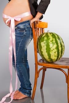 Die schwangere frau und wassermelone. die schwangere frau mit einem dickbauch kostet in der nähe einen stuhl mit einer wassermelone