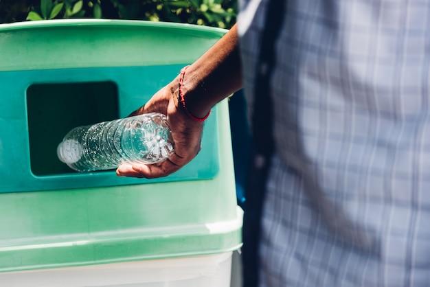 Die schwarze hand des mannes warf eine leere plastikwasserflasche in den recycling-müll