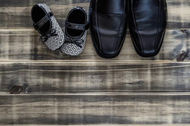 Die schwarzen geschäftsschuhe des vatis und die schwarzweiss-kinderturnschuhe nebeneinander auf rostigem holz des schmutzes, konzept der familie, alleinerziehendes elternteil und vatertag, draufsichtebene legen mit kopienraum.